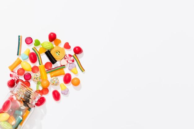 コピースペースと白い背景にカラフルなキャンディーの品揃えをフラット Premium写真