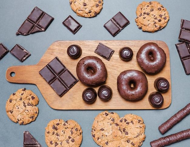 Плоский ассортимент с пончиками на разделочной доске Бесплатные Фотографии