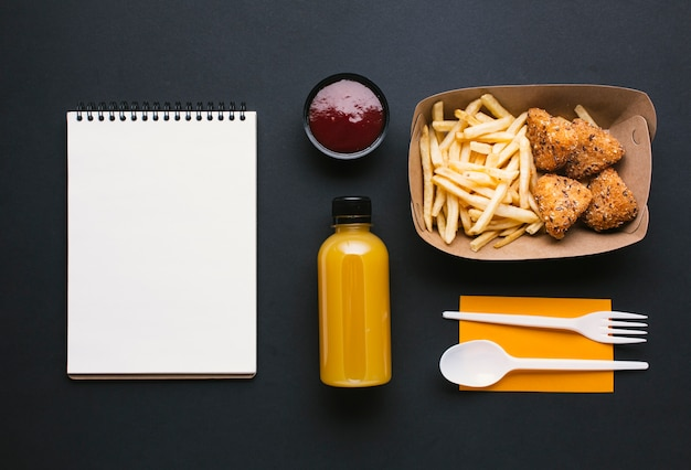 Flat lay assortment with fries and notebook Free Photo