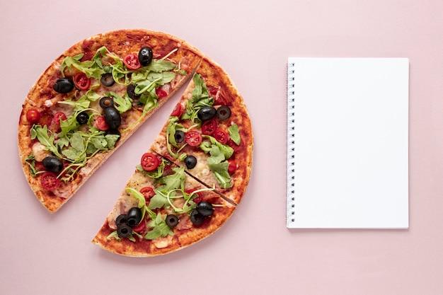 Flat lay assortment with pizza and notebook Free Photo