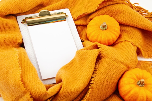 Flat lay autumn composition with notepad and a warm woolen scarf Premium Photo