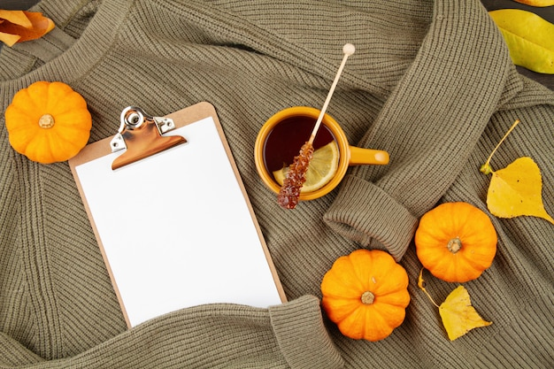 Flat lay autumn composition with tea and a warm woolen sweater Premium Photo