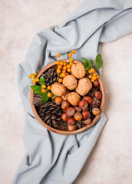 Lay piatto della ciotola autunnale con pigne e tessuto Foto Gratuite
