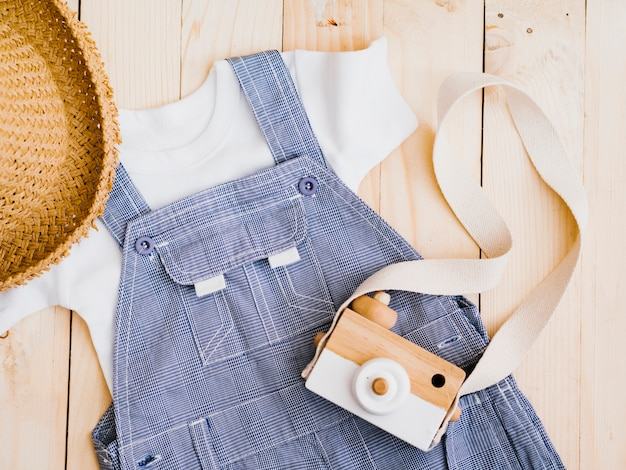 Flat lay baby clothes with photo camera Free Photo