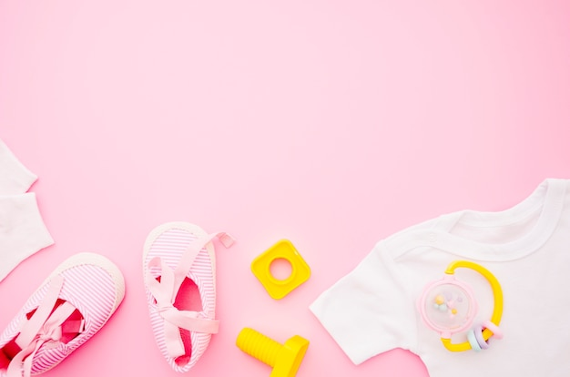 Flat lay baby clothes with pink background Free Photo