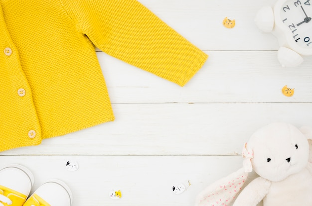 Flat lay baby clothes with wooden background Free Photo
