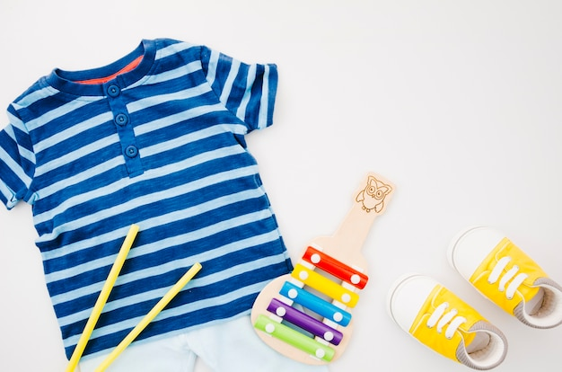 Flat lay baby clothes with xylophone Free Photo