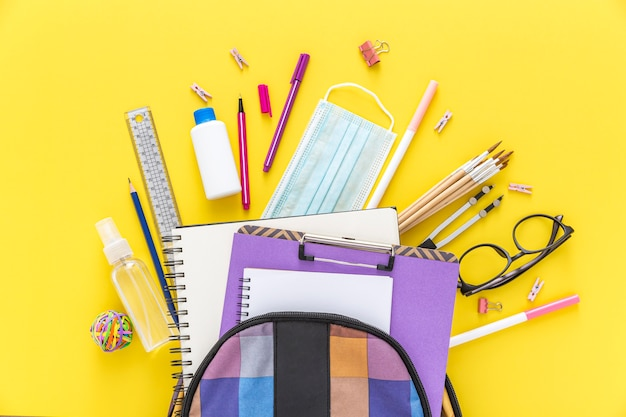 Flat lay of back to school materials with book bag and glasses Premium Photo