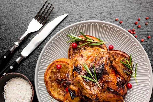 칼 붙이 접시에 평평한 누워 구운 닭고기와 오렌지 슬라이스 무료 사진