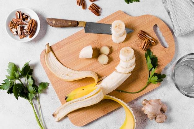 Flat lay of banana on chopping board with ginger Free Photo
