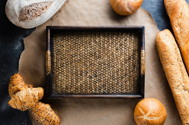 Flat lay of basket and bread on baking sheet Free Photo