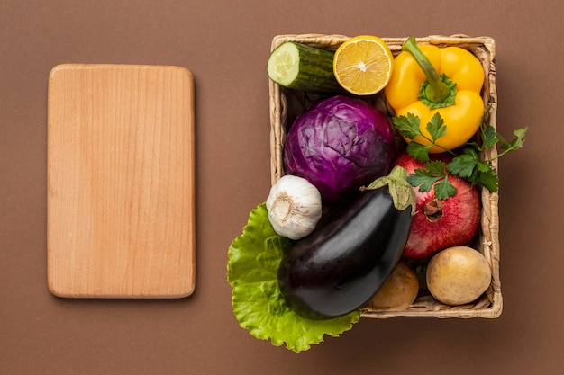 Flat lay of basket of fresh vegetables with chopping board Free Photo