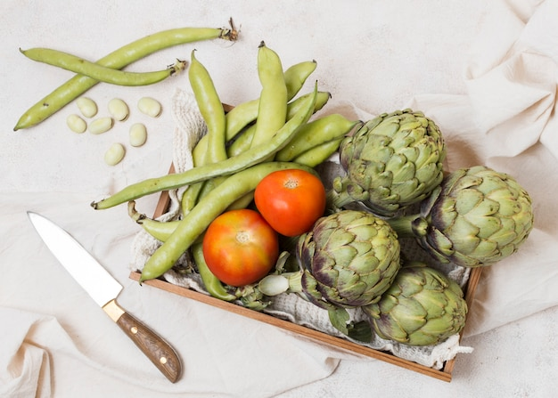 Flat lay of basket with artichokes and tomatoes Free Photo