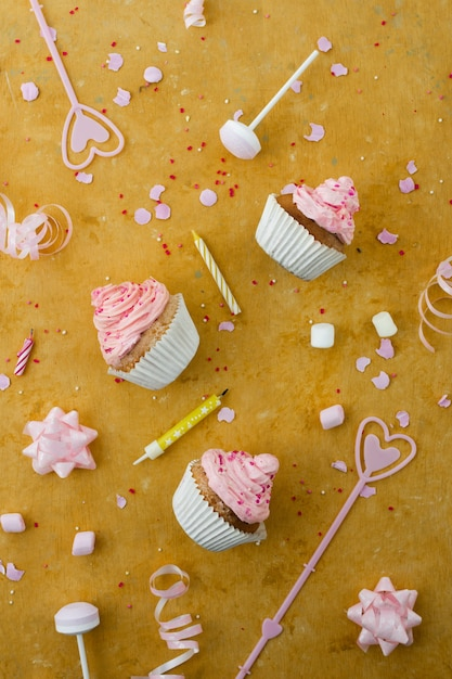 Flat lay of  birthday cupcakes with candles Free Photo