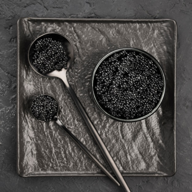 Flat lay of black caviar in bowl and spoons Premium Photo