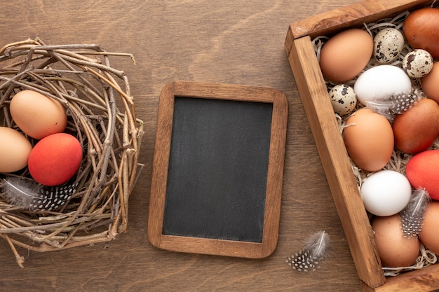 Flat lay of blackboard with next with eggs for easter Premium Photo