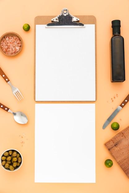 Lay piatto di carta menu vuoto con olive e posate Foto Gratuite