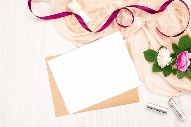 Flat lay blank white greeting card with craft paper envelope, roses flowers, lipstick, ribbon Premium Photo