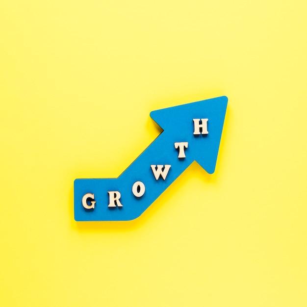 Плоская лежала синяя стрелка роста на желтом фоне Бесплатные Фотографии