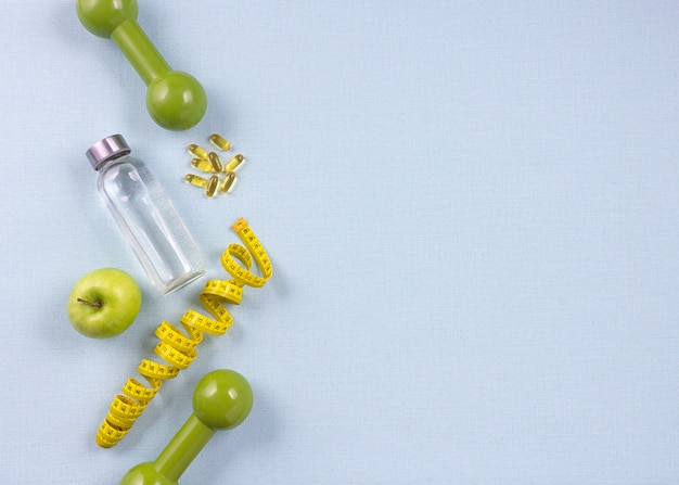 Flat lay bottle of water, measuring tape and fresh green apple on the blue background. weight loss concept. Premium Photo