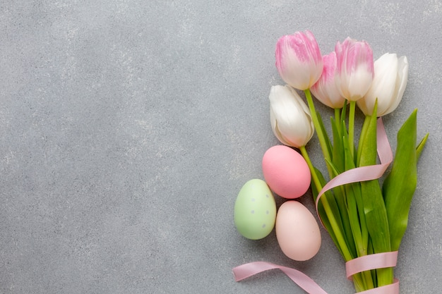 Flat lay of bouquet of tulips with colorful easter eggs Free Photo