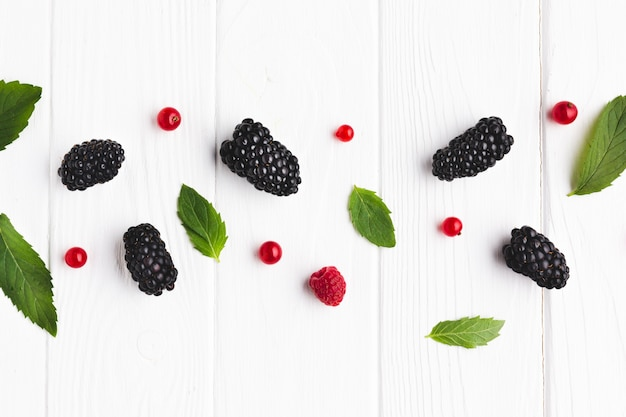 Flat-lay bowl of fresh berries and leaves Free Photo