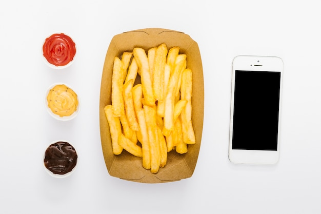 Flat lay box of fries with sauces and smartphone mock-up Free Photo