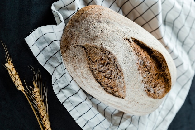 Flat lay of  bread and wheat on cloth Free Photo