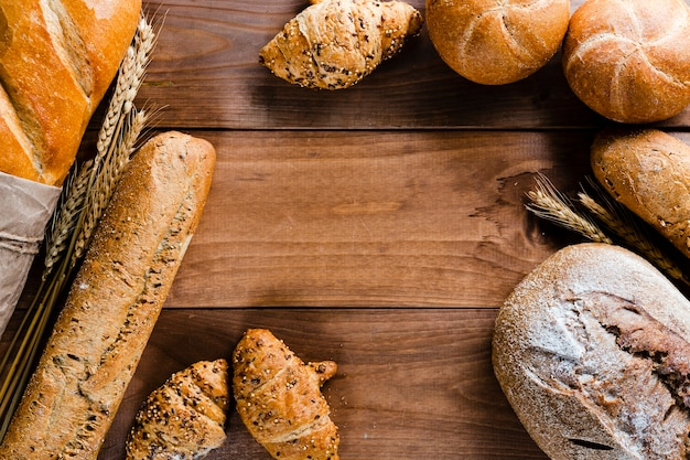 Flat lay of bread on wooden table with copy space Free Photo