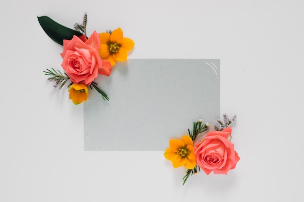 Flat lay bright creative frame of fresh flowers and leaves with gray clean frame for text, natural Premium Photo