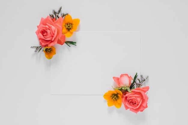 Flat lay bright creative frame of fresh flowers and leaves with white clean blank for text, natural Premium Photo
