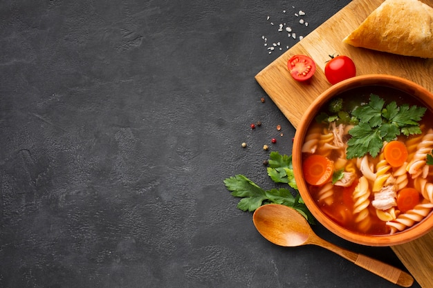 Flat lay broccoli carrots and fusilli soup in bowl with bread tomatoes and wooden spoon with copy space Free Photo