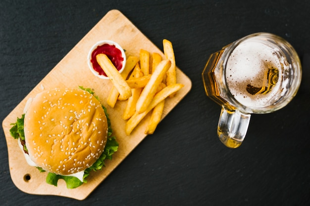 Flat-lay burger and fries on wooden board with beer Free Photo