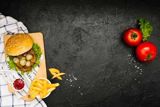 Flat-lay burger and fries on wooden board with copyspace Free Photo
