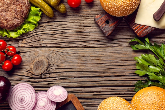 Flat lay burger ingredients on wooden table Free Photo