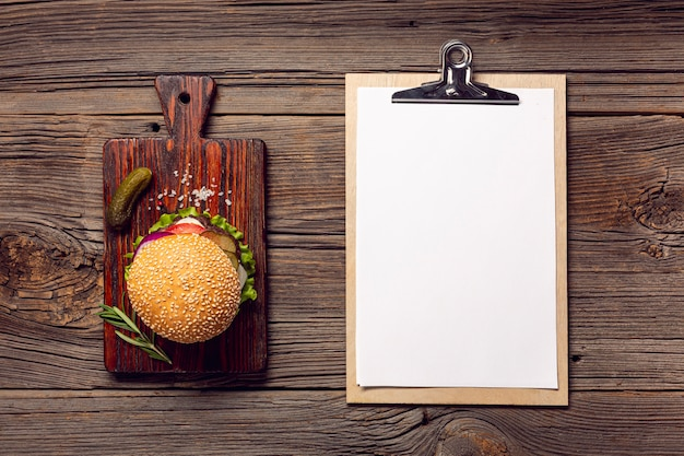 Flat lay burger with mock-up clipboard Free Photo