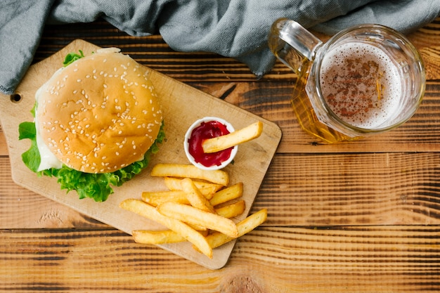 Flat-lay burger on wooden board with beer Free Photo