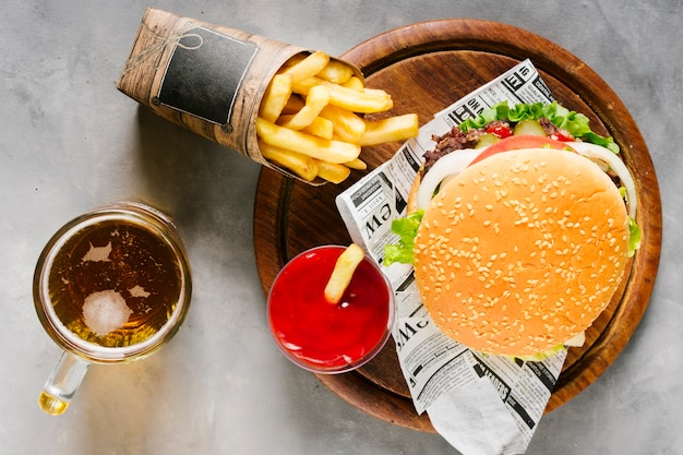 Flat-lay burger on wooden board with fries and beer Free Photo