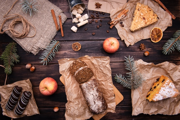 Flat lay of cakes and chocolate desserts with pine and apples Free Photo