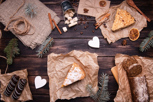 Flat lay of cakes and chocolate desserts with pine and cinnamon Free Photo