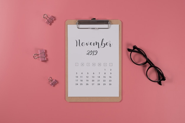 Flat lay calendar with clipboard and glasses on pink background. november 2019. top view. Premium Photo
