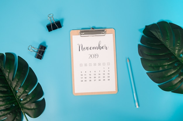 Flat lay calendar with clipboard, palm leaves and pencil on blue background Premium Photo