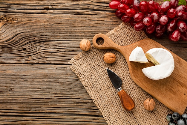 Flat lay camembert grapes and walnuts on wooden cutting board with copy space Free Photo