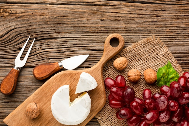 Flat lay camembert grapes and walnuts on wooden cutting board with ustensils Free Photo