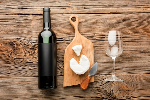 Flat lay camembert on wooden cutting board wine and glass Free Photo