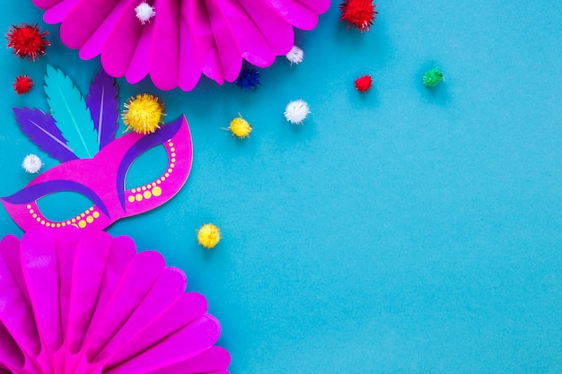 Flat lay of carnival mask and paper fans with pom-poms Free Photo