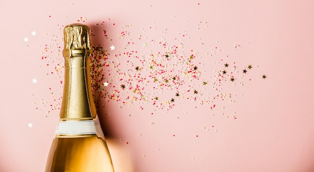Flat lay of celebration. champagne bottle with sprinkles on pink background. Premium Photo