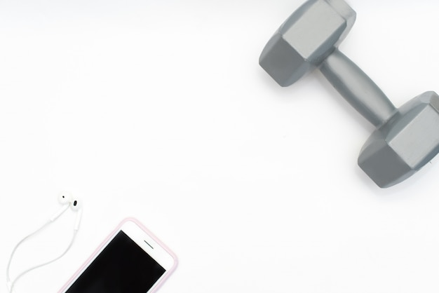 Flat lay of cellphone, red dumbbells and sport equipment on white background. Premium Photo