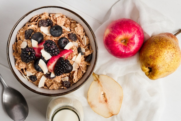 Flat lay cereal and forest fruits in bowl with milk Free Photo