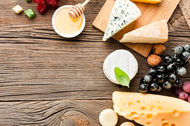 Flat lay cheese assortment grapes and honey with copy space Free Photo